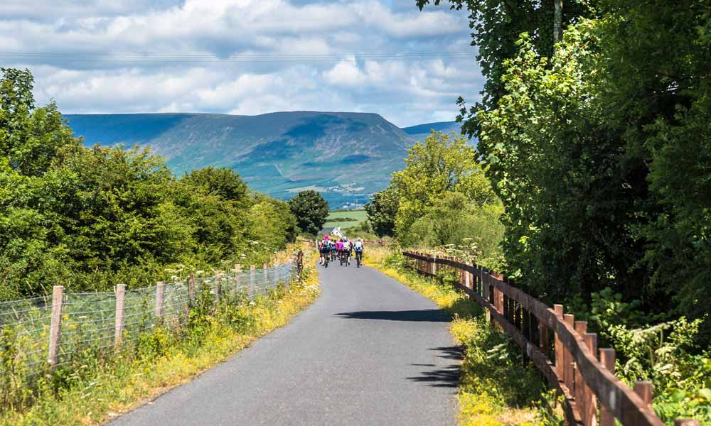 Cyclists on the Waterford Greenway with the Comeragh Mountains in the background