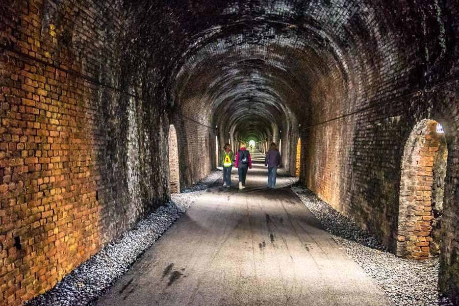 Walkers inside the narrow passages of Ballyvoyle Tunnel on the Waterford Greenway