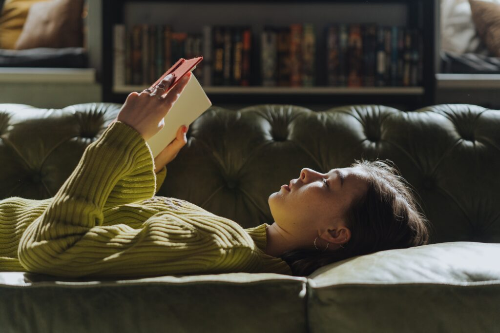 Girl lying down on the couch reading a book